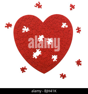 red heart shaped jigsaw puzzle on a white background - Stock Photo