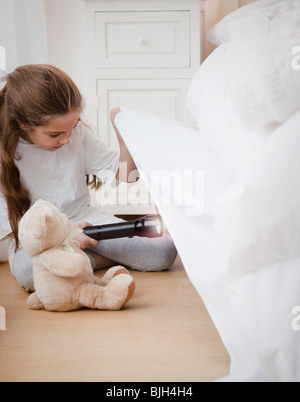 Young girl looking under bed - Stock Photo