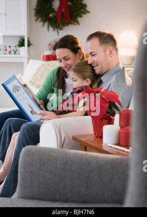 Parents reading to daughter - Stock Photo