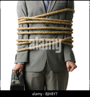 businessman in a full suit tied up with a rope around his mid section - Stock Photo