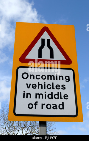 UK Road Sign 'warning oncoming vehicles in middle of road'. - Stock Photo