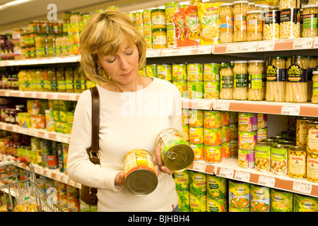 Woman comparing tinned vegetables - Stock Photo