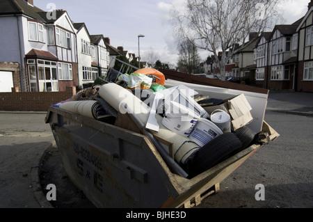 Fully loaded skip in the road readtyto be taken away - Stock Photo