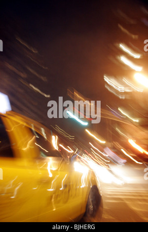 Blurred image of New York taxi at night. - Stock Photo