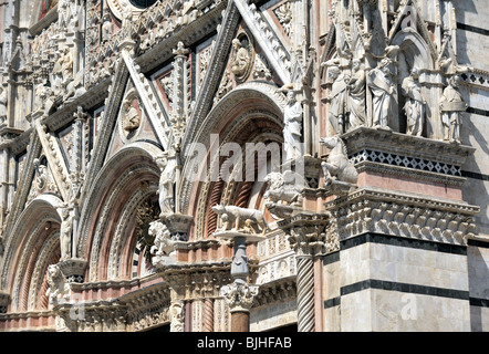 Sienna Cathedral, Tuscany, Italy. The candy-striped main façade of the duomo adorned with beasts and intricate carving - Stock Photo