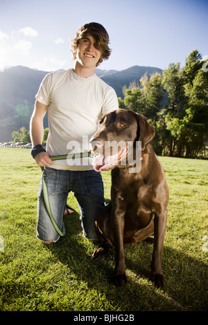 young man kneeling with a chocolate labrador retriever - Stock Photo