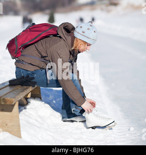 Woman lacing up her ice skates outdoors, Assiniboine River Trail, Winnipeg, Manitoba, Canada. - Stock Photo