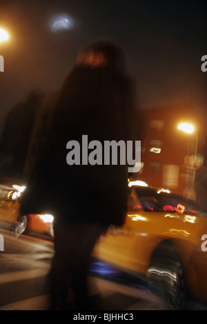 Blurred image of man walking in New York at night. - Stock Photo