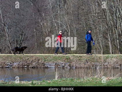 A senior couple a man a woman walking their dog along the canal in a park. Early spring day they are wearing colourful - Stock Photo
