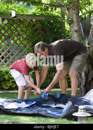 father and son putting up a tent in the backyard - Stock Photo