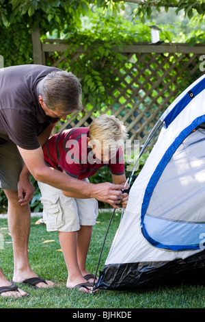 father and son putting up a tent in the back yard - Stock Photo