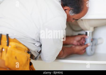 Plumber fixing sink - Stock Photo