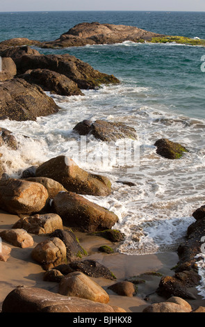 India, Kerala, Kovalam, waves rolling into secluded rocky cove - Stock Photo