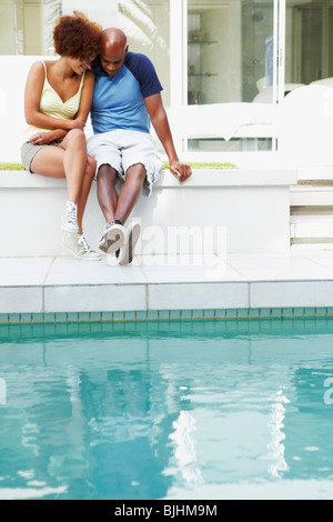 Couple sitting by pool - Stock Photo