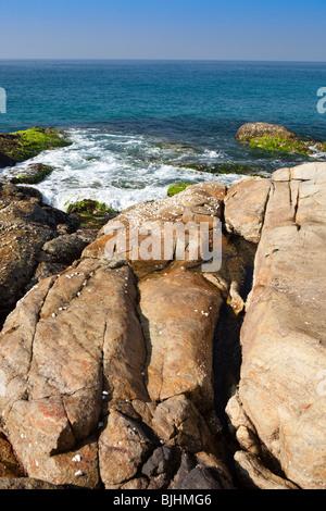 India, Kerala, Kovalam, waves rolling onto rocky headland between Vizhinjam and Lighthouse Beach - Stock Photo