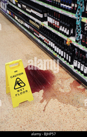 Broken bottle of spilt red wine on supermarket floor - Stock Photo