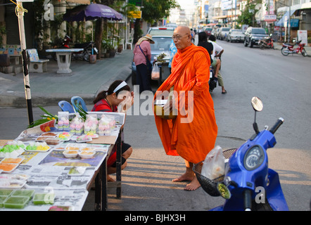 monk receiving alms during his morning rounds in Bangkok Thailand - Stock Photo