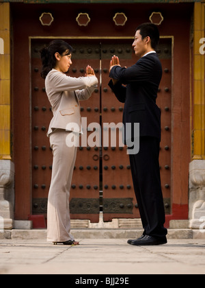 Businesswoman and man facing each other in greeting outdoors - Stock Photo