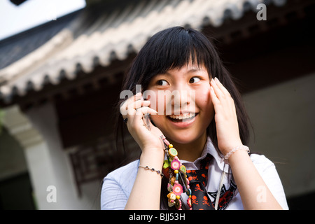 Teenage girl in school uniform smiling with mp3 player - Stock Photo