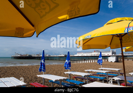 England, East Sussex, Brighton, The Pier with people under sunshade umbrellas by tables on the seafront promenade - Stock Photo