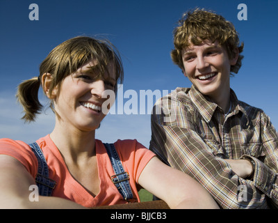 Brother and sister leaning on wooden fence in field with blue skies - Stock Photo