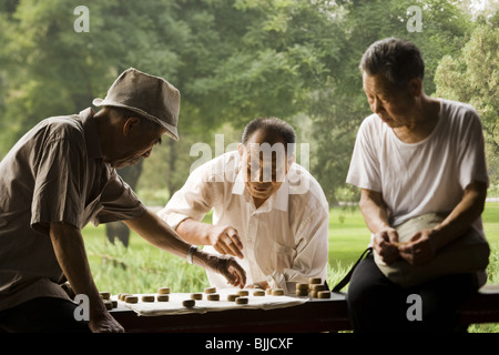 Three men playing board game outdoors smiling - Stock Photo