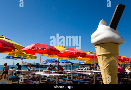 England, East Sussex, Brighton, The Pier with people under sunshade umbrellas by tables on the seafront and giant - Stock Photo