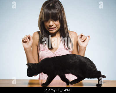 Scared woman with black kitten - Stock Photo