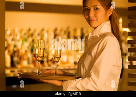 Waitress carrying champagne glasses - Stock Photo