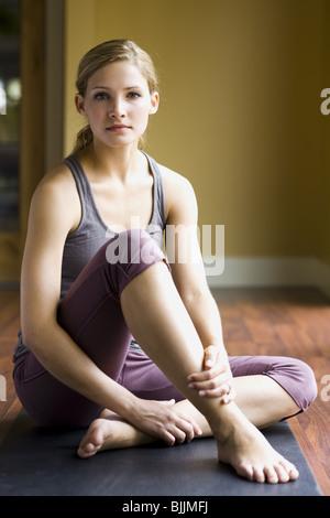 Woman sitting on yoga mat smiling - Stock Photo