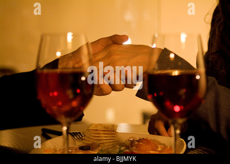 Couple holding hands over a table