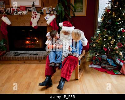 Boys sitting on Santa's lap at Christmas time. - Stock Photo