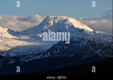 Snow-covered mountain with clouds behind in dramatic evening lighting with shadowed foreground - Stock Photo