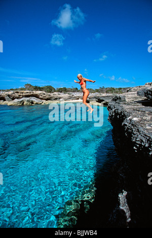 Turks & Caicos Islands, Providenciales, woman jumping off rock wall in red bikini at Northwest Point - Stock Photo