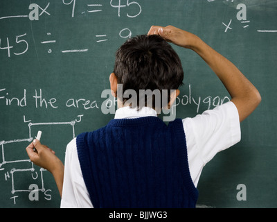 Rear view of boy at chalkboard doing math formulas and scratching head - Stock Photo