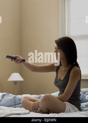 Woman sitting on bed with television remote and tissue - Stock Photo
