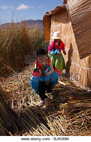 Aymara Indian children on Isla Summa Willjta, one of the Uros man-made floating islands of Lake Titicaca, Peru - Stock Photo