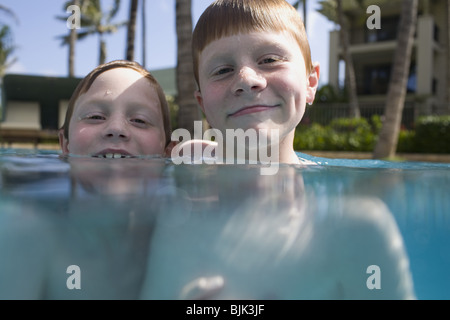 Two boys in outdoor pool smiling - Stock Photo