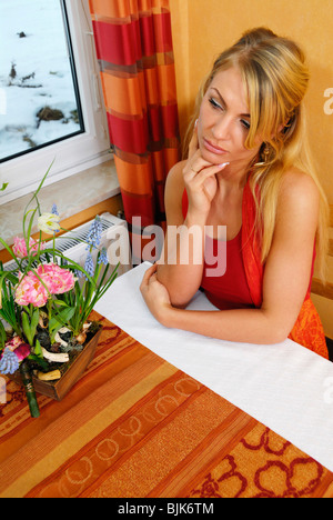 Young woman looking out of the window, sad - Stock Photo