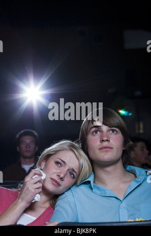 Crying girl and smiling boy watching movie at theater - Stock Photo