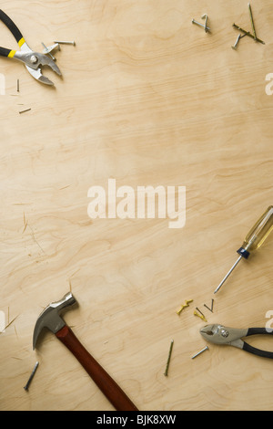 Tools and fasteners on hardwood floor - Stock Photo