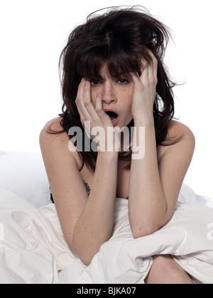 one young caucasian woman awakening yawning tired insomnia in a white sheet bed on studio isolated  white background - Stock Photo