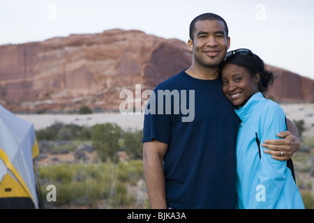 Man and woman hugging outdoors - Stock Photo
