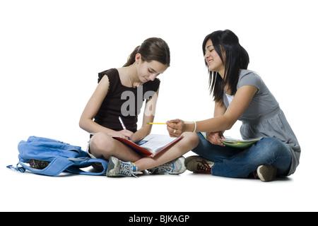 Two girls sitting cross legged doing homework - Stock Photo
