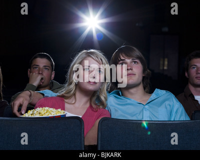 Boy and girl watching film at movie theater smiling - Stock Photo
