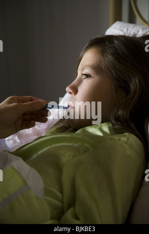Girl in bed with thermometer - Stock Photo