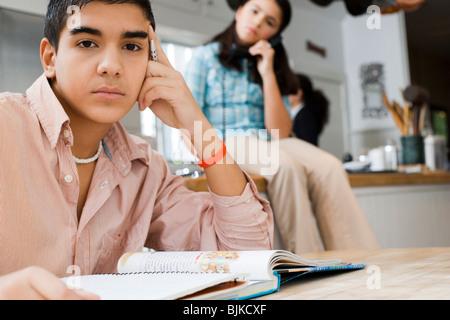 Boy doing homework with girl talking on phone - Stock Photo