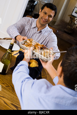 Boy passing chicken to man at table - Stock Photo