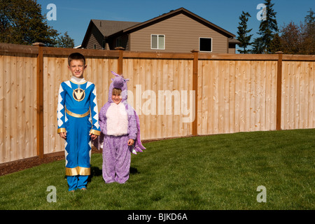 Girl and boy in yard in halloween costumes - Stock Photo