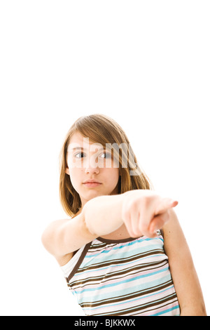 A girl seriously pointing foward with her index finger - Stock Photo